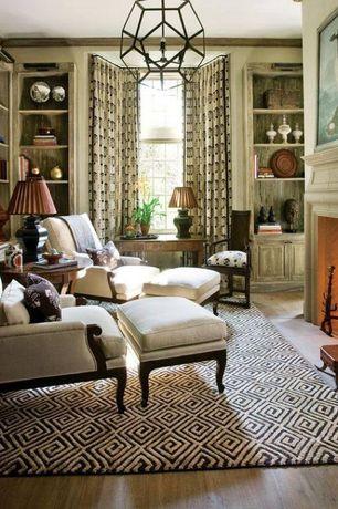 Traditional Living Room with Hardwood floors, Pendant light, Crown molding, Built-in bookshelf, Ashland black / sand area rug