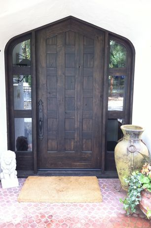 Mediterranean Front Door with picture window, exterior tile floors, exterior interlocking pavers, six panel door