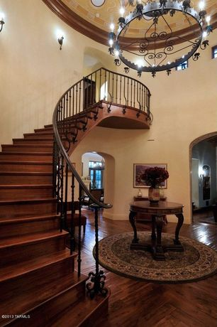 Traditional Staircase with Wall sconce, Hardwood floors, High ceiling, Sunken living room, Crown molding, curved staircase