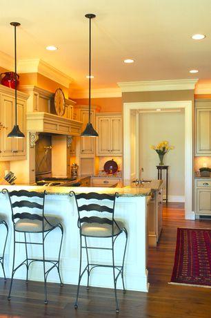Kitchen with Oak flooring, Oversized clock, Breakfast bar, Carpet runner, Wood range hood, Repurposed warehouse lights