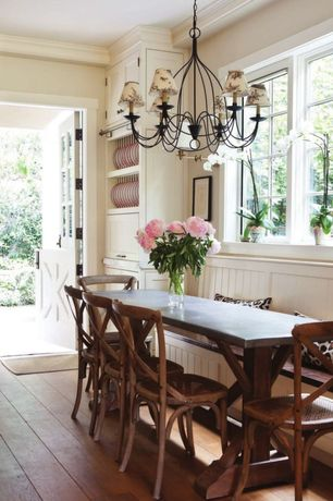 Country Dining Room with Dutch door, Built-in bookshelf, Paint 1, Casement, Standard height, Chandelier, Hardwood floors