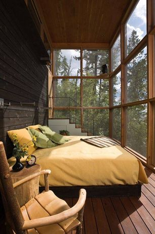 Rustic Guest Bedroom with Barn door, bedroom reading light, can lights, picture window, High ceiling, Hardwood floors