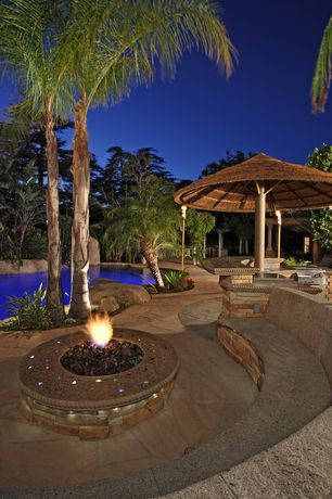 Tropical Patio with exterior stone floors, Outdoor kitchen, Fire pit, Pathway