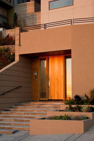 Modern Front Door with exterior tile floors, Raised beds, exterior concrete tile floors, picture window, Deck Railing