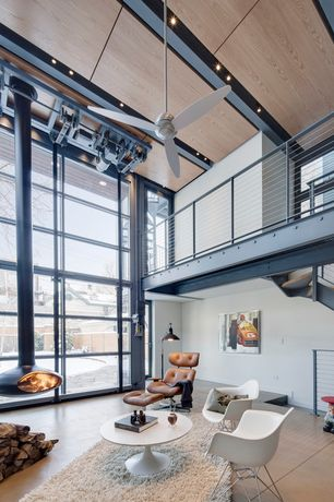 Contemporary Living Room with metal fireplace, Concrete floors, French doors, Ceiling fan, Balcony, picture window, Fireplace