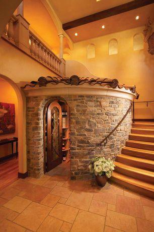 Mediterranean Wine Cellar with Standard height, stone tile floors, Built-in bookshelf, French doors, sandstone tile floors
