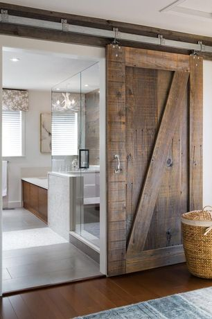 Rustic Master Bathroom with Hardwood floors, Wicker laundry basket, Frameless shower door, White faux antler chandelier