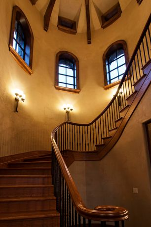 Mediterranean Staircase with Exposed beam, Arched window, curved staircase, Casement, Hardwood floors, Wall sconce