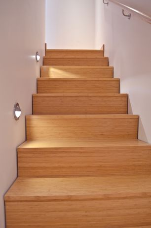 Contemporary Staircase with High ceiling, flush light, Hardwood floors, curved staircase