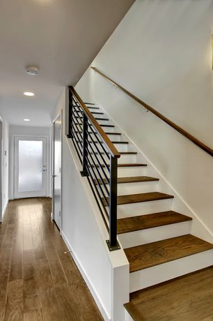 Contemporary Staircase with High ceiling, curved staircase, Hardwood floors, Wall sconce