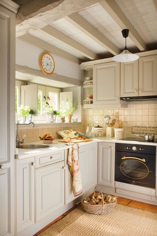 Country Kitchen with Raised panel, Terra cotta tile floor, L-shaped, Exposed beam, Limestone counters, Wall clock