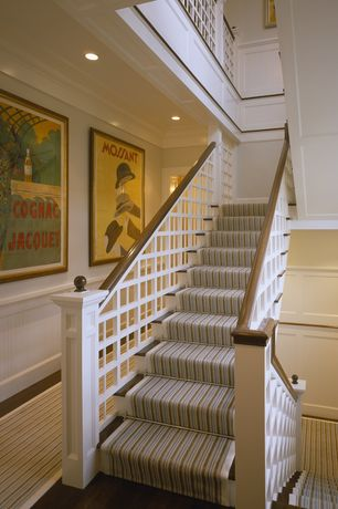 Traditional Staircase with High ceiling, Wainscotting, Hardwood floors, curved staircase