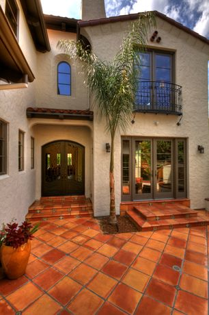 Mediterranean Front Door with exterior terracotta tile floors, Glass panel door, Arched window, exterior tile floors