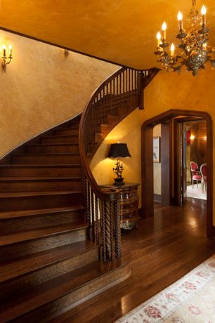 Traditional Staircase with curved staircase, Chandelier, Wall sconce, Standard height, Hardwood floors
