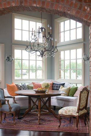 Traditional Dining Room with Chandelier, Exposed brick wall, Paint 1, Wall sconce, Area rug, specialty window, High ceiling