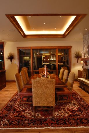 Traditional Dining Room with can lights, Fireplace, picture window, Hardwood floors, stone fireplace, Built-in bookshelf