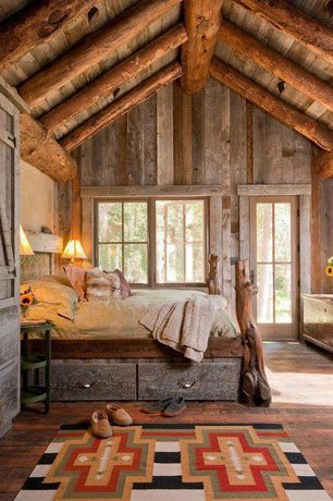 Country Master Bedroom with Reclaimed wood wall, Built-in bookshelf, Hardwood floors, Sun Canyons Dhurrie Rug, Exposed beam