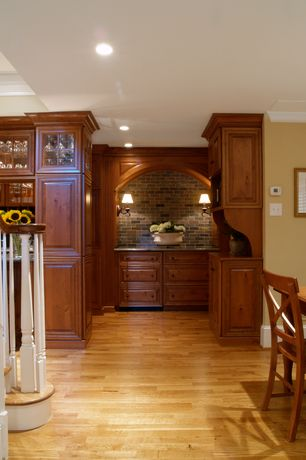 Craftsman Hallway with interior brick, Standard height, Wall sconce, Built-in bookshelf, can lights, Hardwood floors