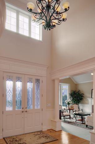 Traditional Entryway with Crown molding, Glass panel door, Columns, Hardwood floors, Chair rail, Chandelier
