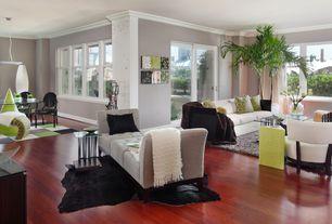 Modern Great Room with Hardwood floors, Upholstered settee, flush light, Crown molding, Cherry hardwood flooring