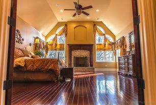 Traditional Master Bedroom with Hardwood floors, Wall sconce, stone fireplace, Ceiling fan, High ceiling