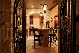Mediterranean Wine Cellar with Crown molding, Pendant light, Wall sconce, specialty door, travertine floors, can lights