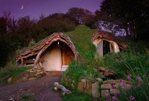 Eclectic Exterior of Home with Straw bale wall construction, Solar panels, Turf roof, Skylight, Hobbit house, wales