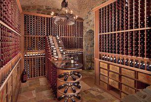 Traditional Wine Cellar with Built-in bookshelf, travertine floors, Chandelier