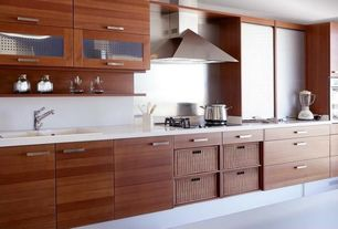 Contemporary Kitchen with Flush, Corian counters, Glass panel, drop-in sink, European Cabinets, Wall Hood, wall oven