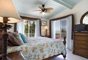 Tropical Guest Bedroom with Pendant light, terracotta tile floors, Built-in bookshelf, Ceiling fan