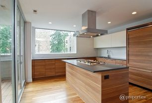 Contemporary Kitchen with Concrete counters, Undermount sink, Laminate floors, Glass panel door, Flush, L-shaped