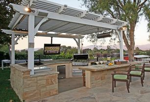 Traditional Patio with Outdoor kitchen, Trellis, exterior stone floors, exterior awning