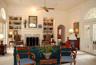 Traditional Living Room with Arched window, French doors, stone fireplace, High ceiling, Built-in bookshelf, Carpet