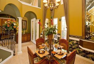 Tropical Dining Room with Crown molding, Chandelier, travertine floors, interior wallpaper, Chair rail, Columns