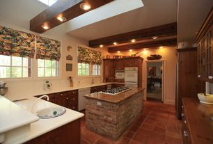 Country Kitchen with Raised panel, Kitchen island, terracotta tile floors, Wine refrigerator, Skylight, High ceiling