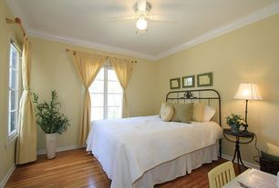 Cottage Guest Bedroom with Ceiling fan, Crown molding, Casement, Standard height, Hardwood floors