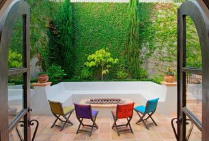 Eclectic Patio with French doors, exterior stone floors, Fire pit, Fence, Raised beds