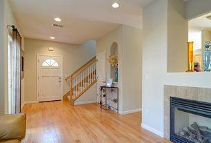 Modern Entryway with metal fireplace, Cement fireplace, Hardwood floors, Glass panel door