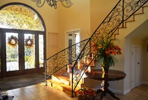 Mediterranean Entryway with Traditional Mahogany Round Table with Gold Accents, French doors, Built-in bookshelf