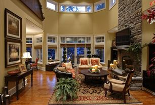Traditional Living Room with High ceiling, can lights, stone fireplace, Casement, picture window, Laminate floors, Fireplace