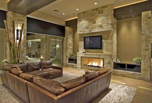 Contemporary Living Room with Standard height, can lights, Hardwood floors, Fireplace, picture window, Wall sconce