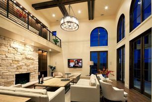 Contemporary Living Room with Hardwood floors, Loft, High ceiling, Arched window, can lights, Stacked stone fireplace