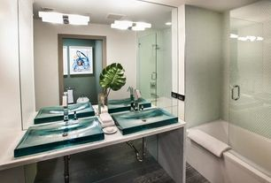 Contemporary Master Bathroom with tiled wall showerbath, Simple marble counters, Laminate floors, frameless showerdoor