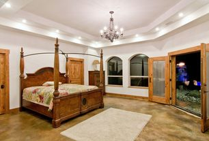 Craftsman Master Bedroom with French doors, Concrete floors, Built-in bookshelf, Chandelier, Arched window, High ceiling