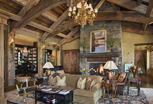 Rustic Great Room with stone fireplace, Built-in bookshelf, Wall sconce, Chandelier, Hardwood floors, Hardwood flooring