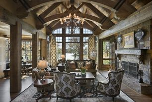 Country Great Room with French doors, Transom window, Chandelier, Built-in bookshelf, Exposed beam, stone fireplace, Columns