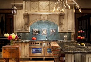 Country Kitchen with One-wall, Glass Tile, Custom hood, Chandelier, Flat panel cabinets, Pendant light, Double oven gas range