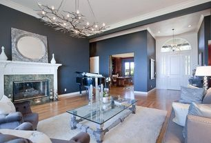 Living Room with Chandelier, Laminate floors, Shades of light circle in a square stamped metal mirror, stone fireplace