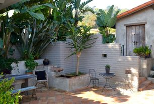 Mediterranean Patio with Cement wall, Spanish tile roof, Bistro table and chairs, exterior tile floors, Fence, Raised beds