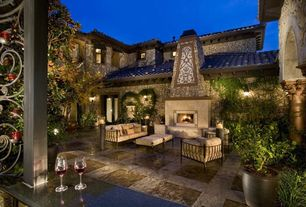 Mediterranean Patio with exterior stone floors, outdoor pizza oven, French doors